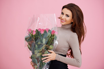 Happy woman holding pink roses