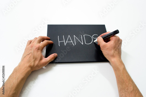 "two hand writing ""hands"" on a black background"