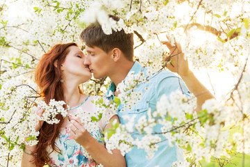 man and woman kissing in flower garden