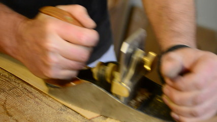 Luthier working in workplace with a wood planer