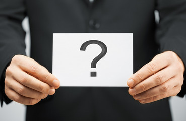 man in suit holding card with question mark