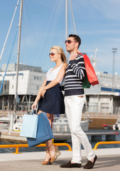 young couple in duty free shopping bags