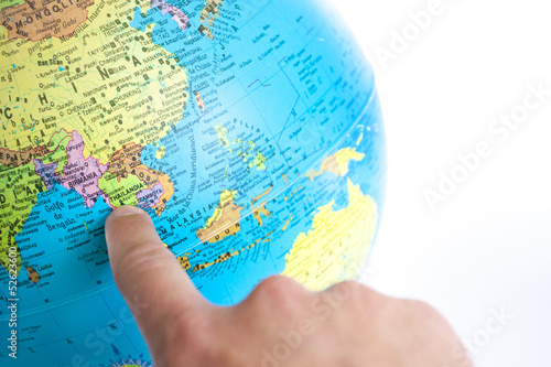 A Finger pointing to Thailand in a World Globe