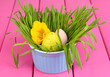 Easter eggs in bowl with grass on pink wooden table close up