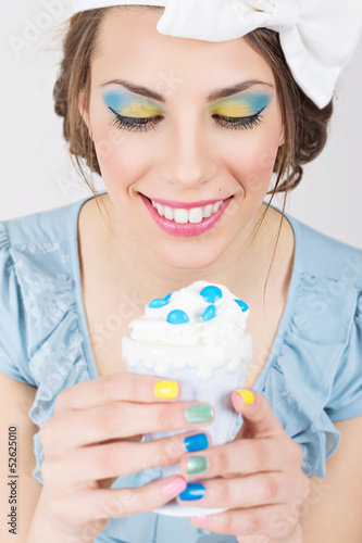 Pin-up girl with colorful makeup and manicure holding ice-cream