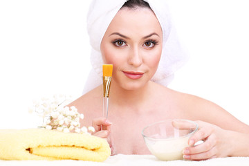 Beautiful young woman with cream for face mask and towel