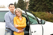 Portrait of happy beautiful couple standing near the car