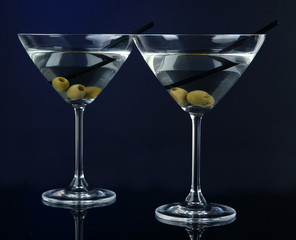 Martini glasses with olives on dark blue background