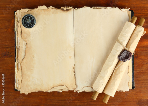 Open old book, scrolls and compass on wooden background