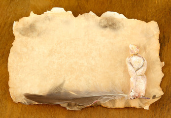 Old paper with figurine, on wooden background
