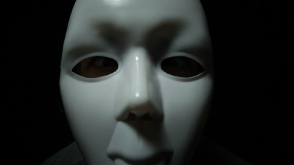Scary masked man over black background