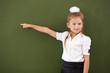 Scoolgirl standing near blackboard