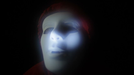 Furious scary masked man in darkness
