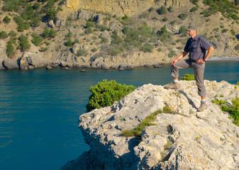 Male hiker on a stony sea shore