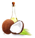 Coconut with oil, milk and palm leaves isolated on white.