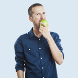 Cheerful beautiful man eating apple, isolated over white backgro