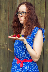 Red-haired girl holding a strawberry.