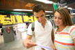 Couple in train station checking trip tickets