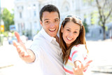 Cheerful couple with hands towards camera