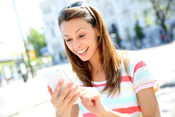 Beautiful girl using smartphone in town