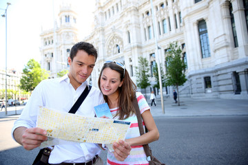 Tourists reading map in front of Palacio de Comunicaciones