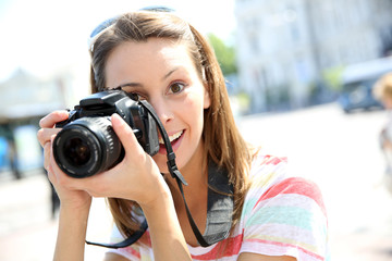Portrait of young woman holding reflex camera