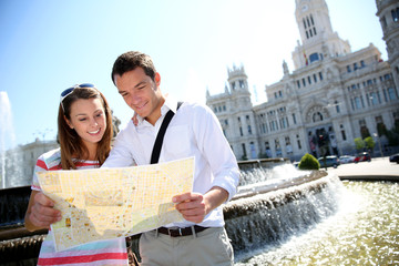 Couple of tourists reading map in Plaza de Cibeles, Madrid