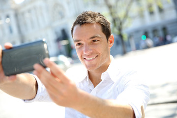 Smiling man taking picture of himself with smartphone