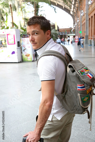 Smiling tourist with backback in train station