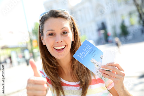 Cheerful girl in Madrid holding city guide and tousist pass
