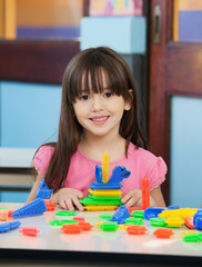 Little Girl With Construction Blocks In Classroom