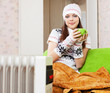 woman relaxing near oil heater