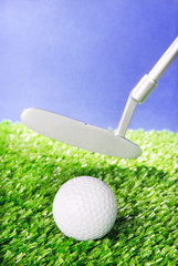Golf ball and club on green field grass against blue sky