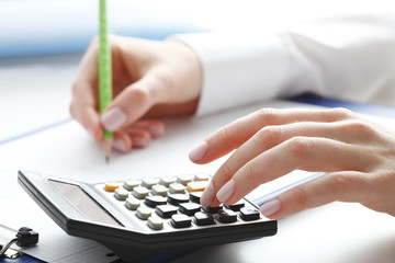 Financial data analyzing. Counting on calculator.