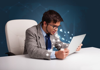 Angry man sitting at dest and typing on laptop with message icon