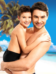 happy smiling father hugs son at tropical beach