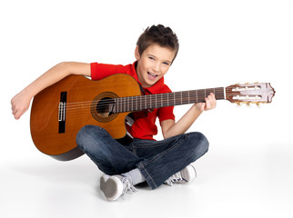 Smiling boy is playing the acoustic guitar