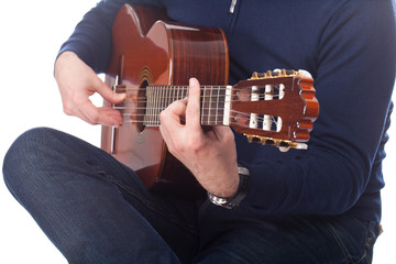 Brown guitar in hands of the guy playing it
