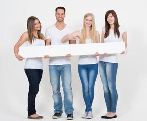 junge Leute halten längliches Werbeschild