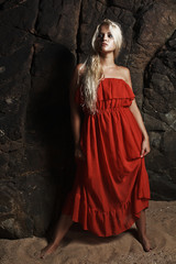Beautiful blond woman in red dress near the rock