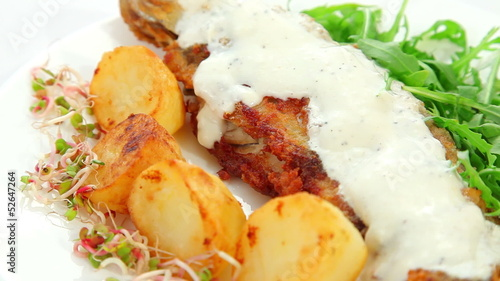 Fried fish dish with sauce - fish, salad, potatoes, sprouts