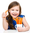 Cute little girl is eating carrot