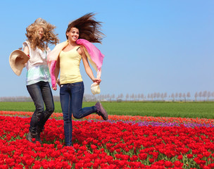 two women in a red tulip field