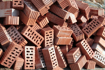 Heap of red ceramic hollow bricks