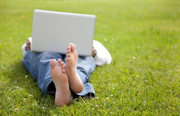 Hombre tumbado en la hierba consultando el portatil