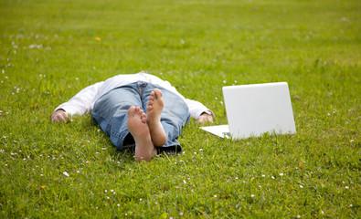 Hombre joven descansando en la hierba con el portatil