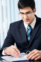 Portrait of writing businessman working at office