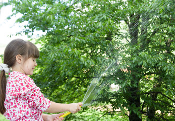 Little girl playing with hose and water