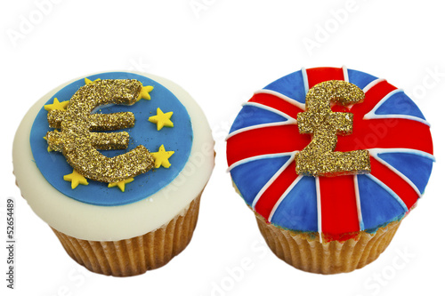 Two iced cupcakes decorated with Euro and Sterling signs.
