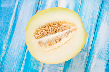 Half of a ripe Galia melon on wooden boards, view from above